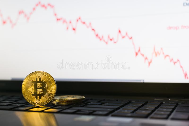 Bitcoin cryptocurrency coin standing on laptop keyboard with descending chart on background stock images