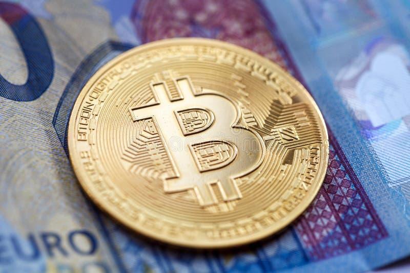 Bitcoin-cryptocurrency, eine Goldmünze, liegt auf einer ZwanzigEuro-Rechnung lizenzfreie stockfotografie
