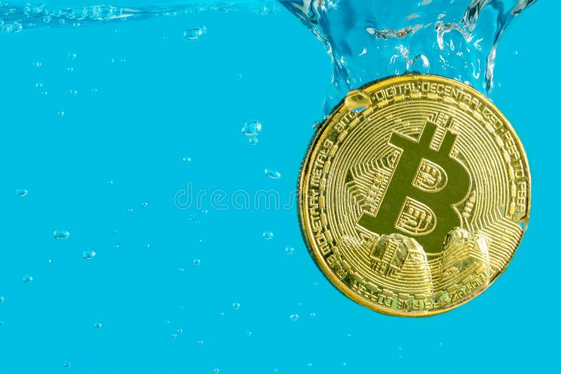 Bitcoin cryptocurrency gold coin falls into the water with bubbles sinking on a blue background, the concept of falling bitcoin cr stock photo