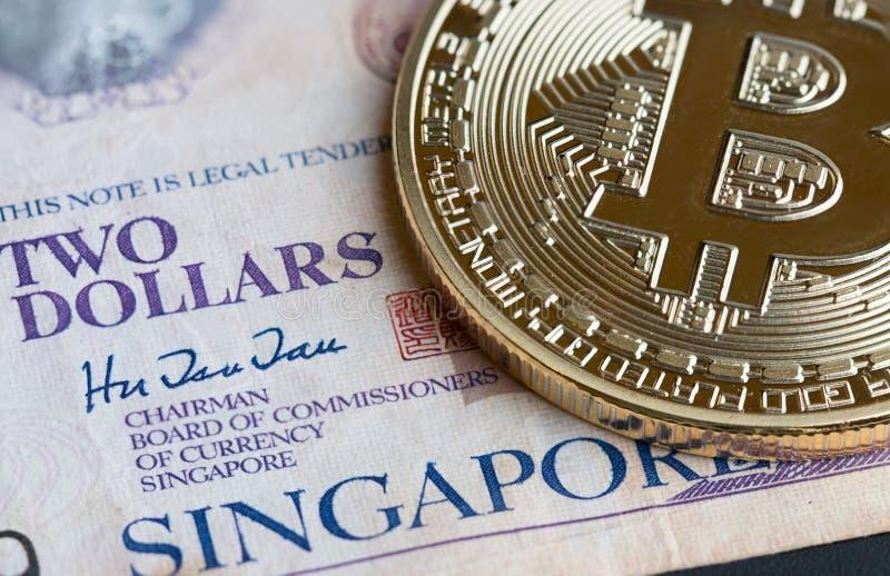 Bitcoin Cryptocurrency ist Digital-Zahlungsgeld, Goldmünzen mit b-Kurzzeichenelektronischer schaltung auf Singapur-Rechnung lizenzfreie stockfotos