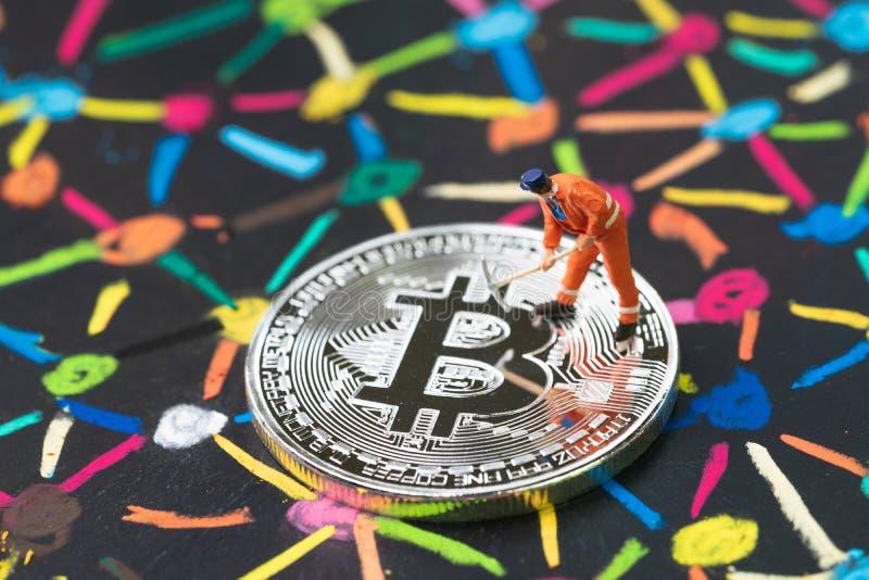 Bitcoin-cryptocurrency Konzept, Miniaturarbeitskraft, die auf körperlicher glänzender Silbermünze auf bunter Pastellkreidemarkier stockbilder
