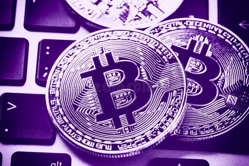 Bitcoin cryptocurrency monety na laptop klawiaturze Zamyka w górę Pozafioletowy stonowanego zdjęcie stock