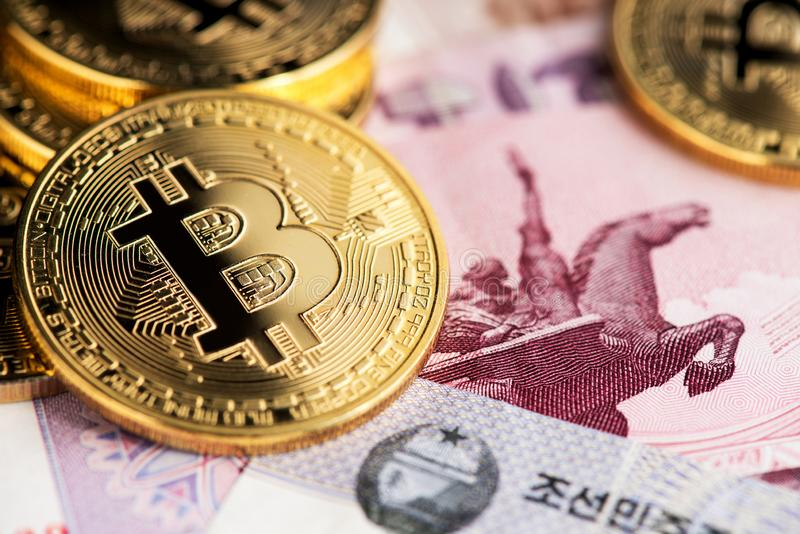 Bitcoin cryptocurrency on North Korean Won close up image. Bitcoin BTC cryptocurrency coins virtual money on North Korean Won currency anknotes close up image royalty free stock photography