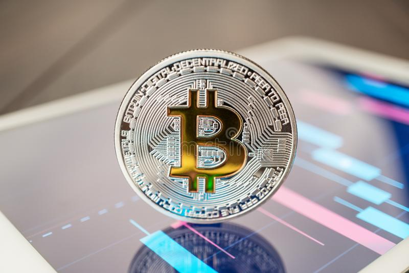 Close-up photo of bitcoin cryptocurrency physical coin on the tablet computer showing stock market charts. Trading bitcoin concept stock image