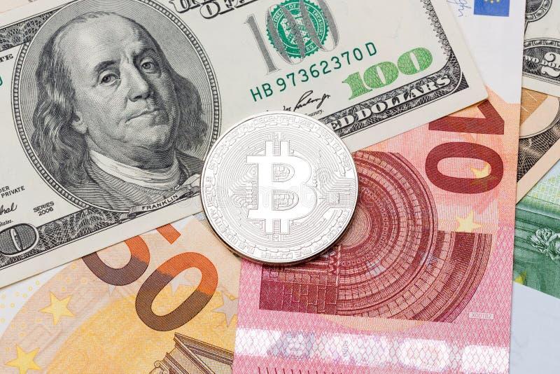 Bitcoin d'argento sugli euro e sul fondo del dollaro fotografie stock libere da diritti