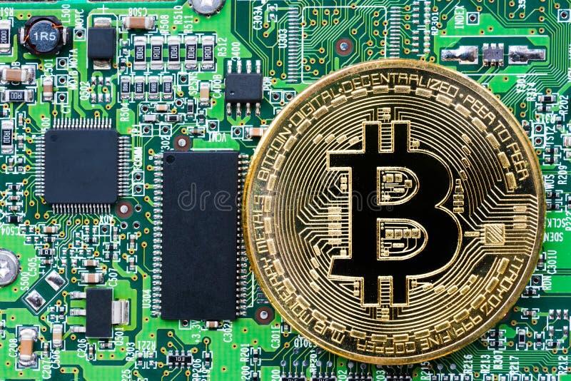 Bitcoin d'or de couleur sur une carte électronique photo stock