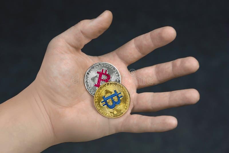 Bitcoin d'or et argenté à disposition d'isolement sur le fond noir photos libres de droits