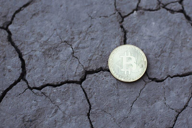 Bitcoin de la moneda en la tierra agrietada Pluma, lentes y gráficos fotos de archivo