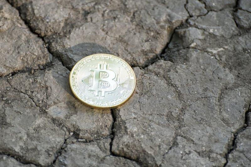 Bitcoin de la moneda en la tierra agrietada Pluma, lentes y gráficos foto de archivo libre de regalías