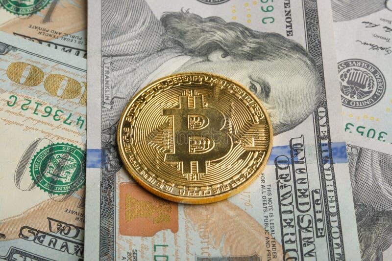 Bitcoin de la moneda de oro en cuentas del ciento-dólar imagenes de archivo