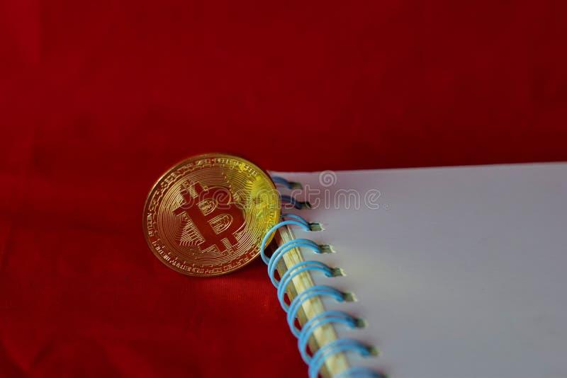 Bitcoin de la moneda y un cuaderno aislado en el fondo rojo, extracci?n de la moneda crypto imagen de archivo libre de regalías