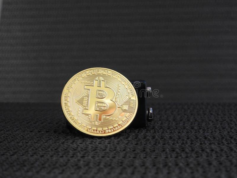 Bitcoin de oro con la batería foto de archivo