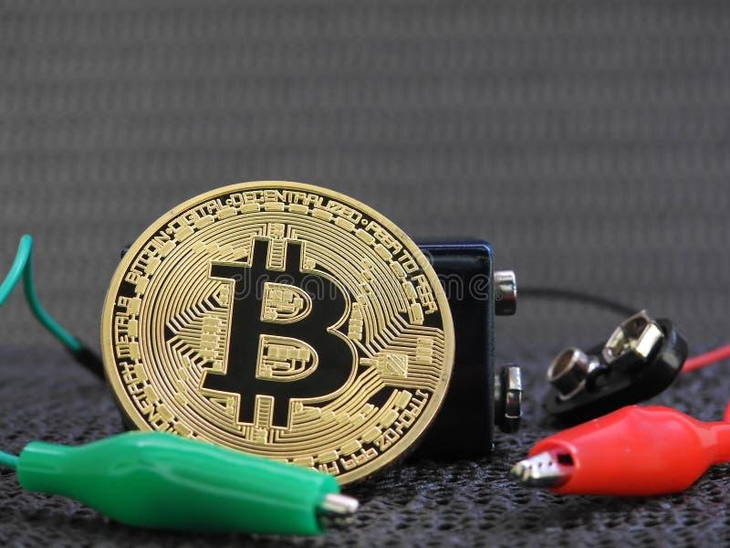 Bitcoin de oro con la batería y los clips de cocodrilo fotografía de archivo