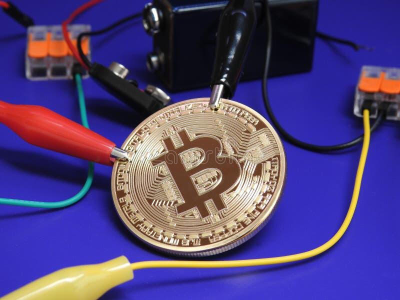 Bitcoin de oro con la batería y los clips de cocodrilo foto de archivo libre de regalías