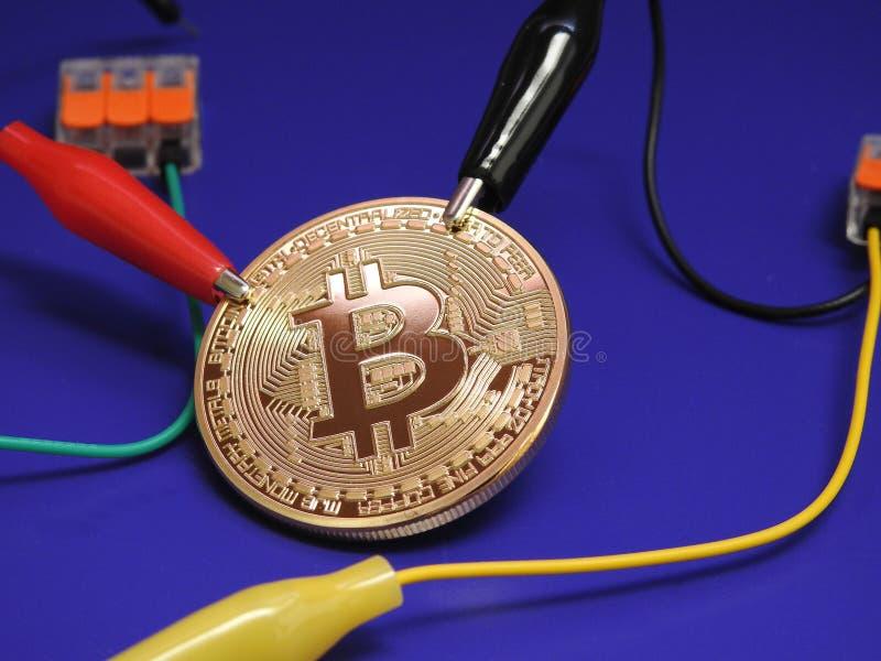 Bitcoin de oro con los clips de cocodrilo fotos de archivo libres de regalías