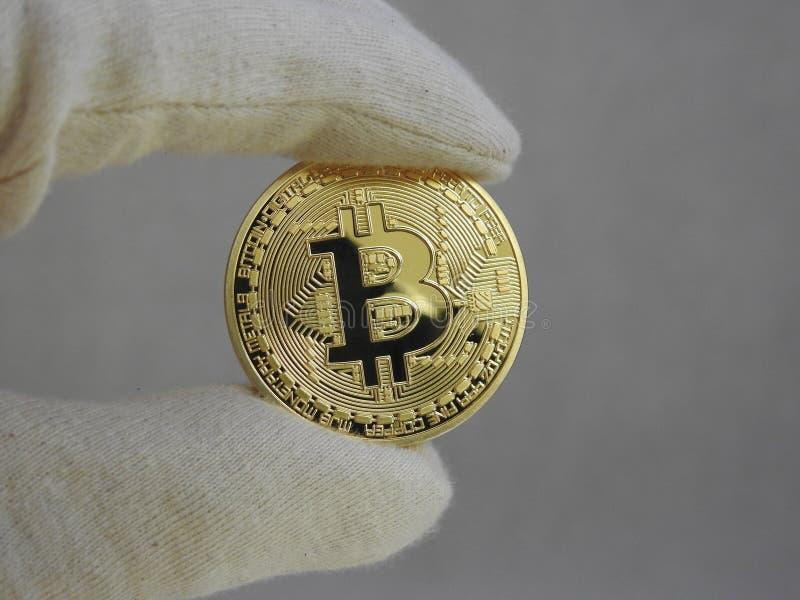 Bitcoin de oro dirigido con los guantes imágenes de archivo libres de regalías