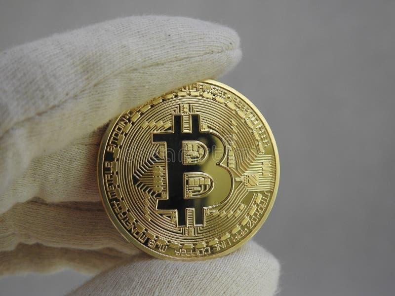 Bitcoin de oro dirigido con los guantes foto de archivo