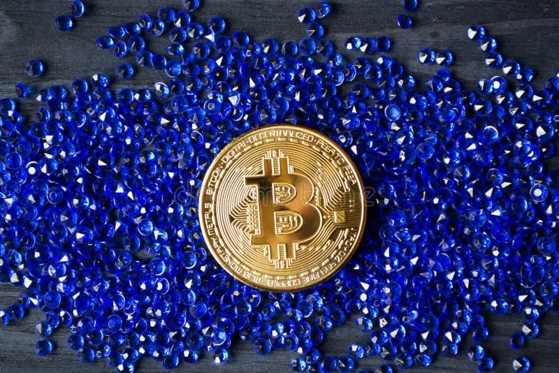 Bitcoin de oro en las joyas azules imagenes de archivo