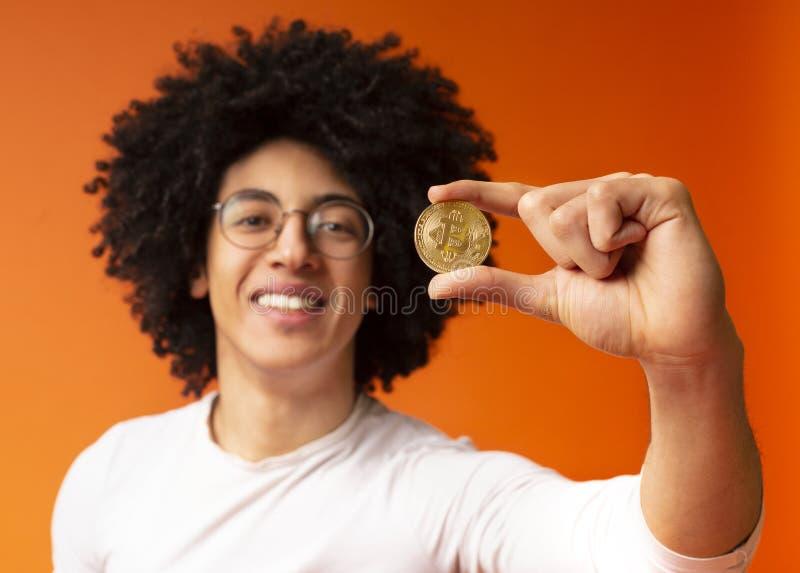 Bitcoin de oro en primer afroamericano de la mano del hombre foto de archivo libre de regalías