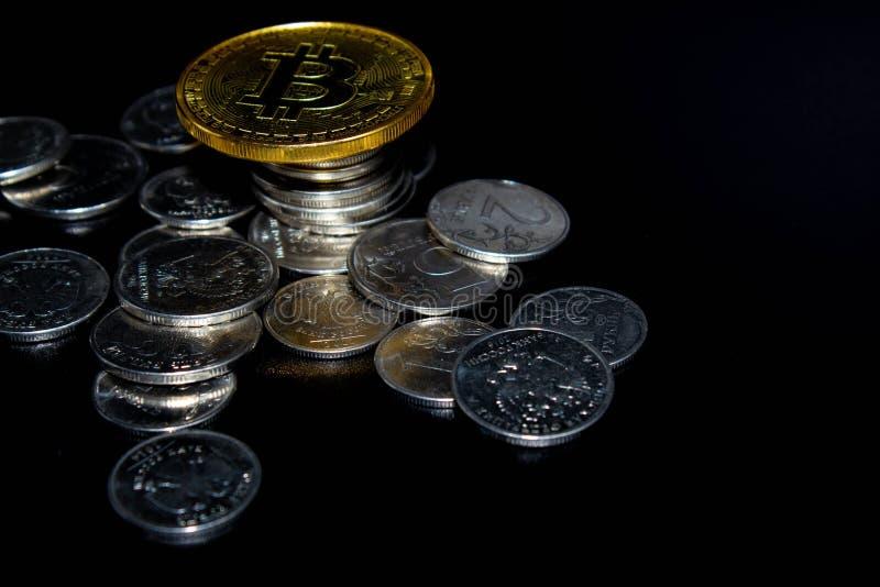 Bitcoin de oro en un fondo negro, dinero imagenes de archivo