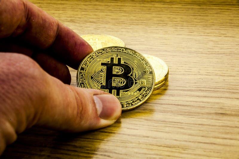 Bitcoin de oro en una mano del ` s del hombre Símbolo de una nueva moneda virtual ilustración 3D fotografía de archivo