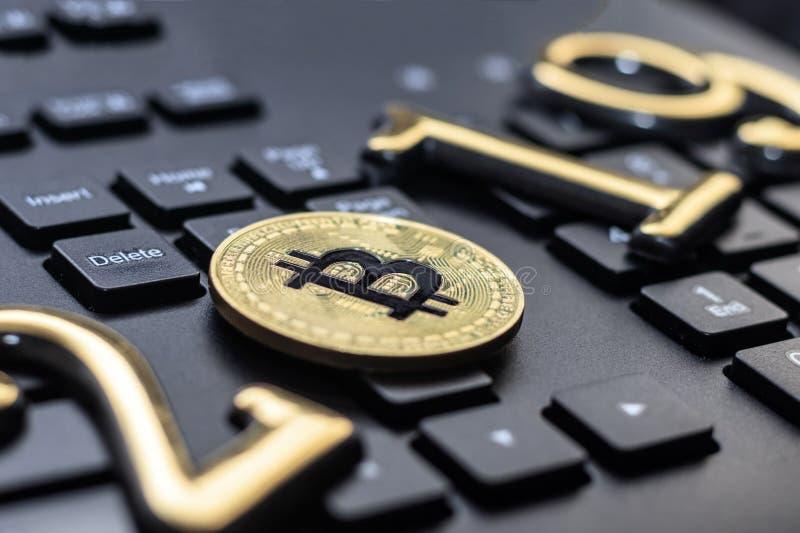 bitcoin de oro miente en el teclado de un color oscuro La inscripción 2019 Hay un tono foto de archivo libre de regalías