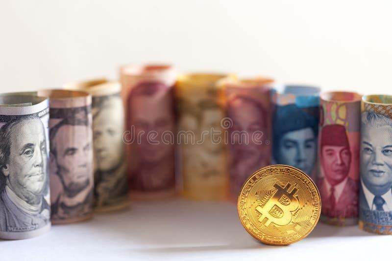 Bitcoin de oro y billetes de banco imagen de archivo libre de regalías