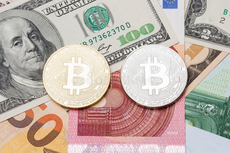 Bitcoin de plata y de oro en euros y fondo del dólar imágenes de archivo libres de regalías