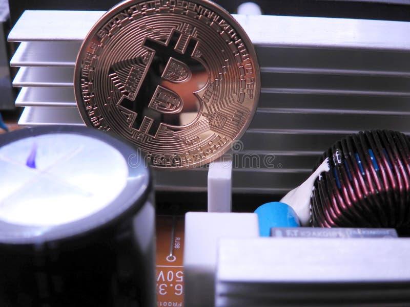 Bitcoin delante de componentes electrónicos y del refrigerador de aluminio imagen de archivo