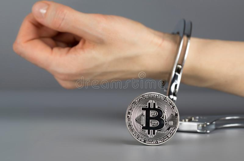 Bitcoin delante de la mano en esposas imagen de archivo