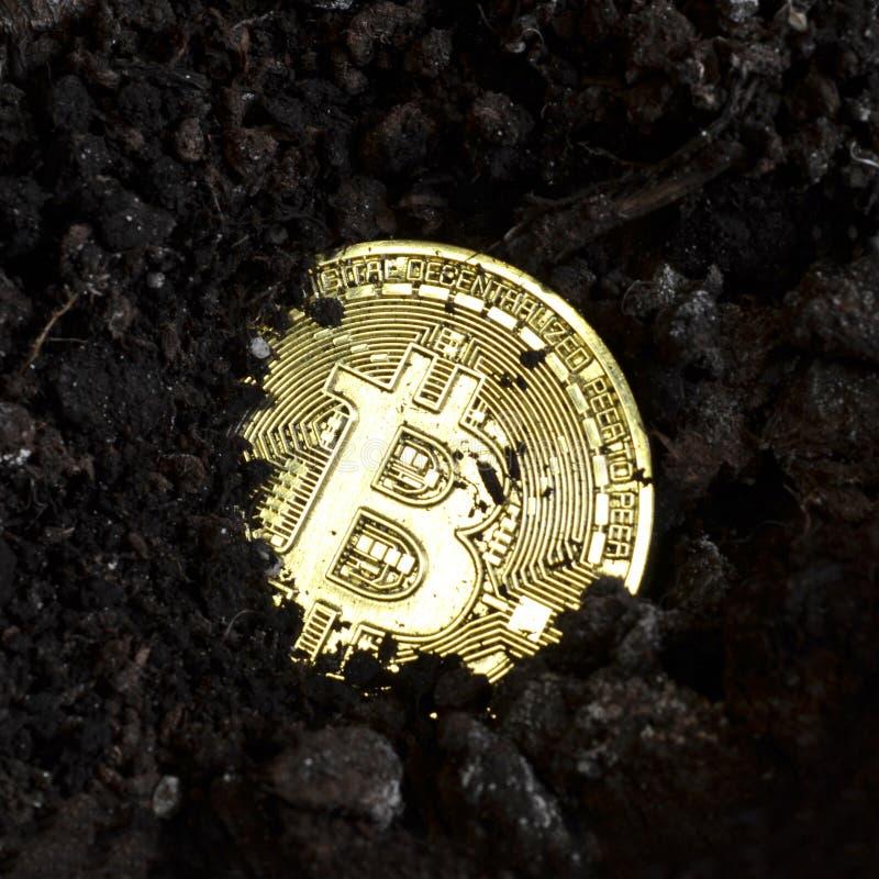 Bitcoin della moneta di oro sepolto nella terra fotografie stock