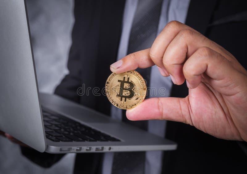 Bitcoin della tenuta della mano con il computer portatile fotografie stock libere da diritti