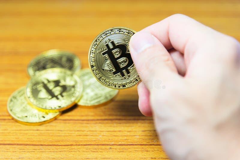 Bitcoin in der Hand mit einem unscharfen bitcoin Hintergrund stockfoto