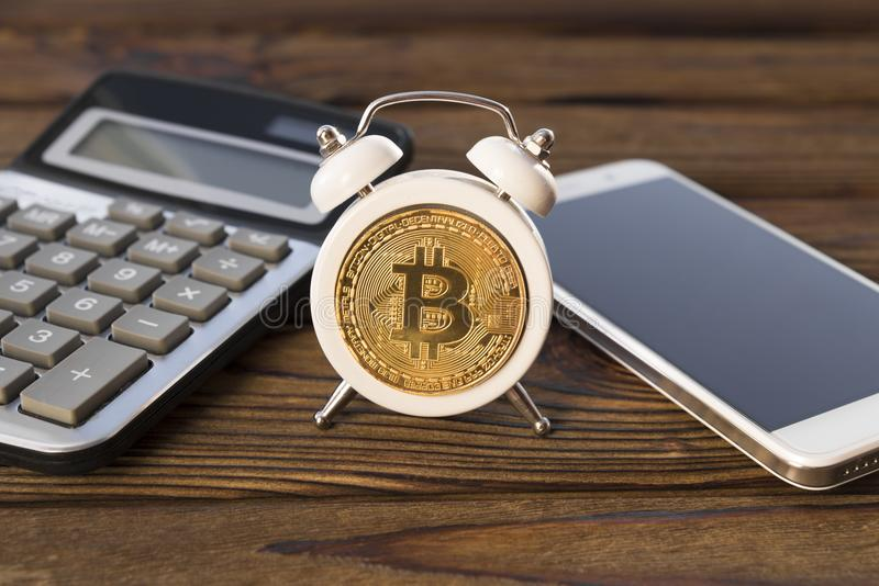 Bitcoin, despertador, calculadora, smartphone en un fondo de madera foto de archivo