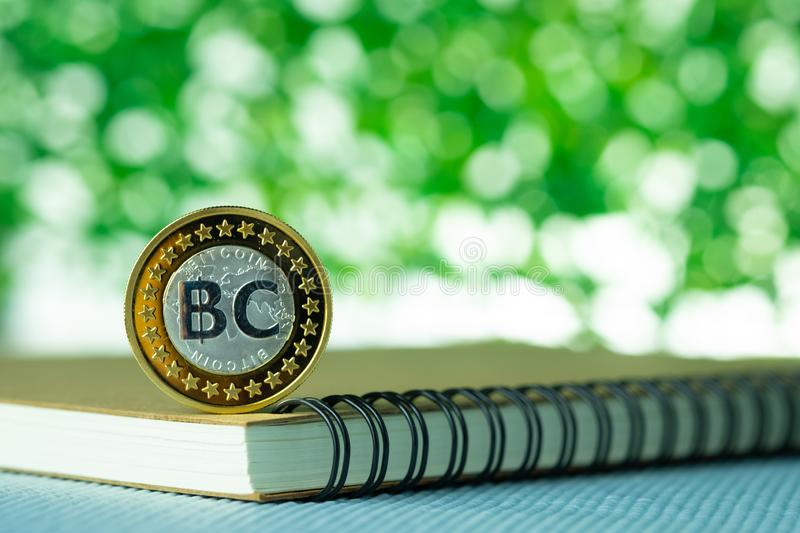Bitcoin digital currency,  bit-coin on green blurred bokeh background, Cryptocurrency money concept stock photography