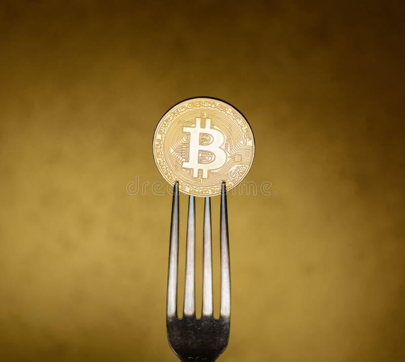 Bitcoin dorato dentro con la forcella d'argento fotografia stock