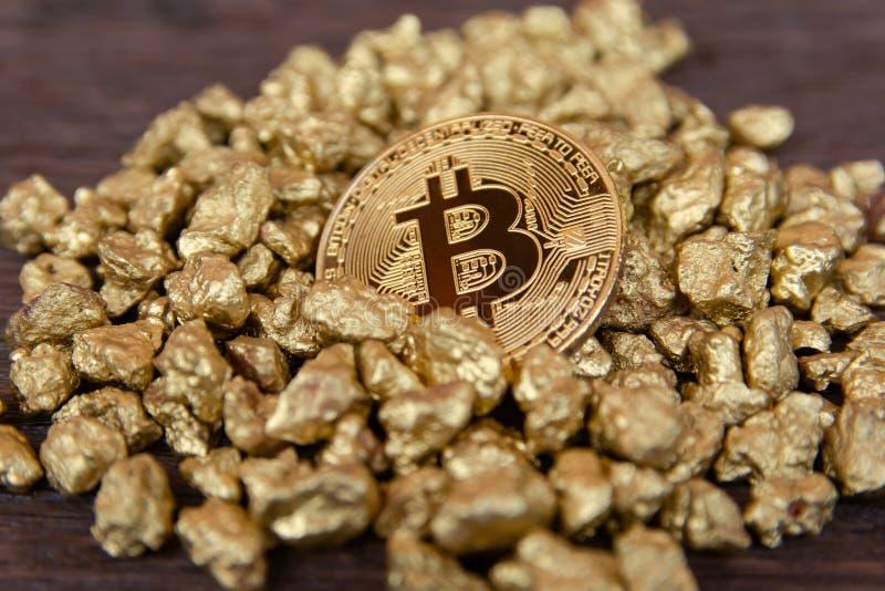 Bitcoin dorato sul monticello della pepita di oro su fondo di legno scuro fotografie stock libere da diritti