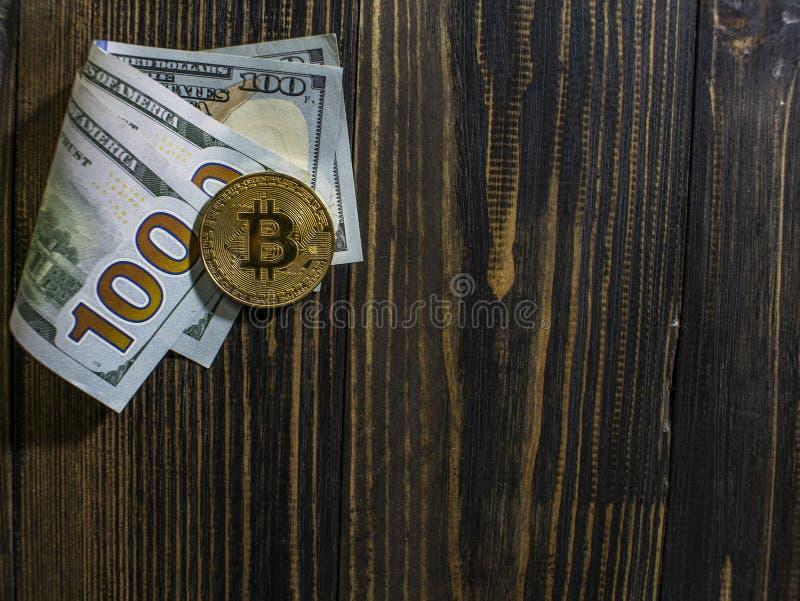 Bitcoin dourado em d?lares americanos Close-up da moeda de Digitas em um fundo de madeira Moedas reais do bitcoin em c?dulas de c
