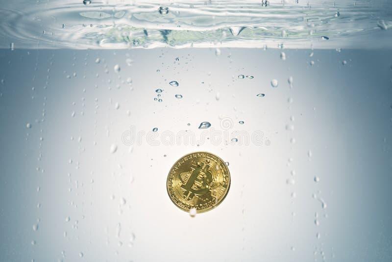 Bitcoin dourado que está sendo deixado cair na opinião da água foto de stock royalty free