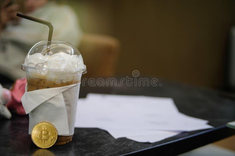BitCoin e caffè ghiacciato sulla tavola di legno, fondo vago, per fotografia stock