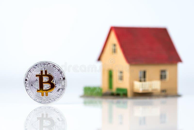 Bitcoin e a casa privada modelam no fundo claro Tema dos bens imobiliários Conceito de comprar uma propriedade para a moeda cript imagem de stock