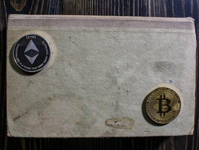 Bitcoin e Ethereum em um livro velho que encontra-se em uma tabela de madeira dinheiro virtual novo