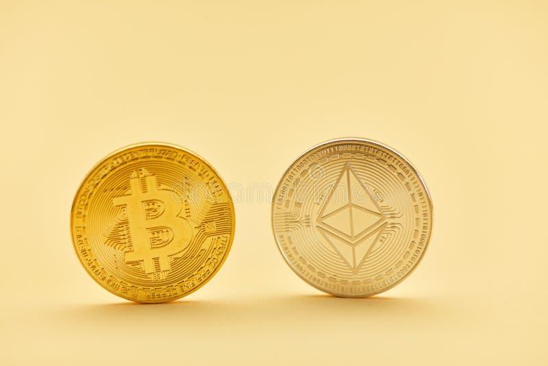 Bitcoin e moneta dell'etere in oro ed argento fotografia stock libera da diritti