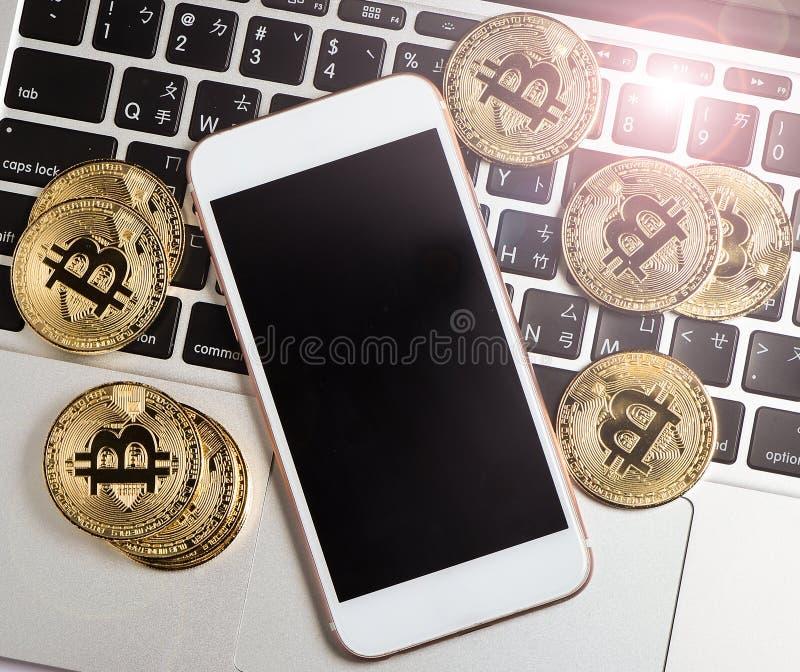 Bitcoin e o iphone no portátil com um halo de incandescência, Bitcoin são uma moeda cripto imagem de stock royalty free