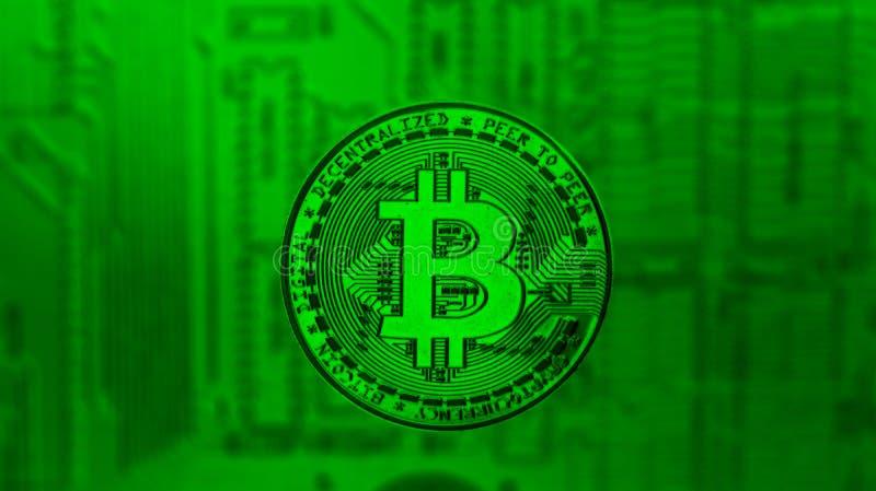 Bitcoin en bronze au-dessus de carte mère de PC dans la teinte verte photographie stock