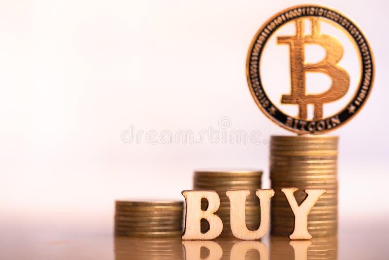 Bitcoin en la palabra COMPRA de la pila de las monedas y del bloque de madera foto de archivo