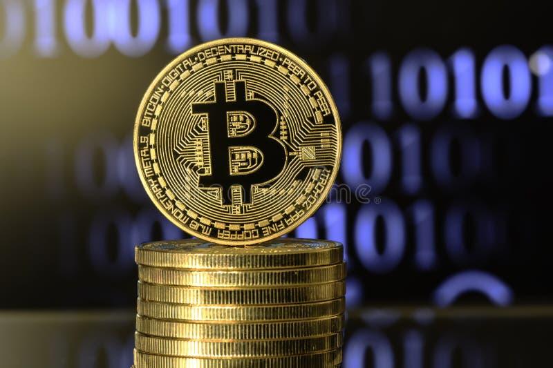 Bitcoin encima de la pila del dinero, contra fondo borroso fotos de archivo