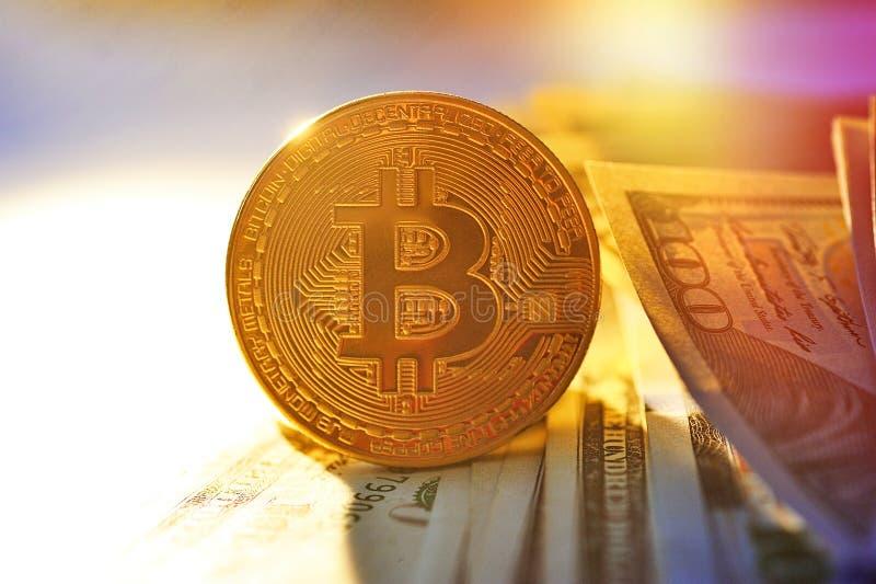 Bitcoin es una moneda de oro en billetes de dólar Pluma, lentes y gráficos fotografía de archivo libre de regalías