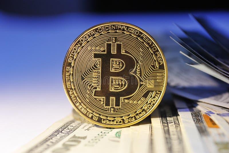 Bitcoin es una moneda de oro en billetes de dólar Pluma, lentes y gráficos fotos de archivo libres de regalías