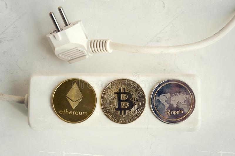 Bitcoin, Ethereum and Ripple coins lying on power strip extension cord with 3 sockets,. Largest cryptocurrencies by market capitalization, cryptocurrency royalty free stock photo